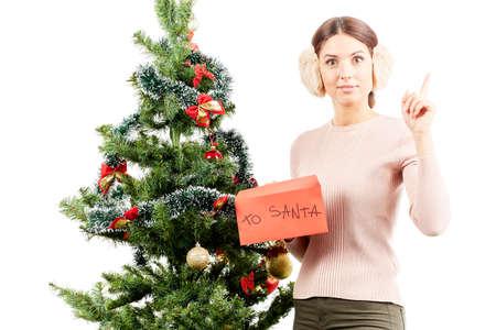 Portrait of beautiful woman in earmuffs posing near Christmas tree