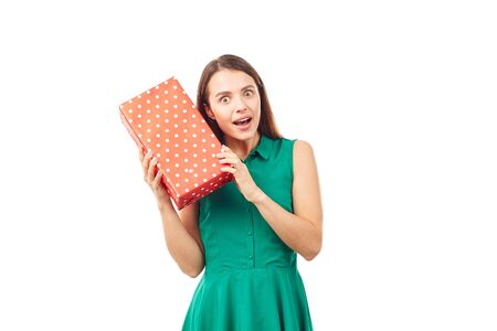 Portrait of young woman holding gift box wrapped in red paper