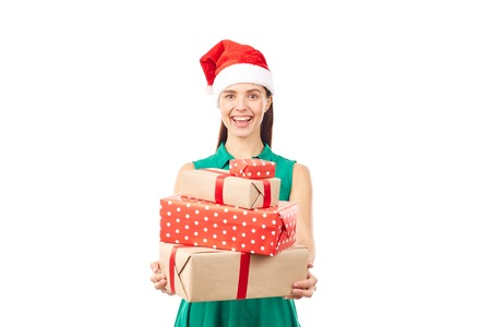 Portrait of young woman in Santa hat holding stack of Christmas gifts on white background