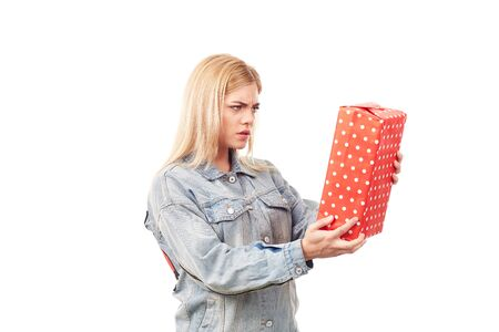 Young blonde in denim jacket holding gift box Stock Photo
