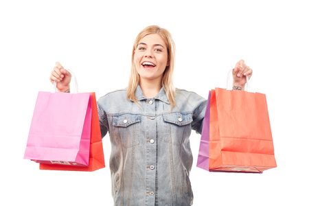 Portrait of young woman in denim jacket holding shopping bags in both hands