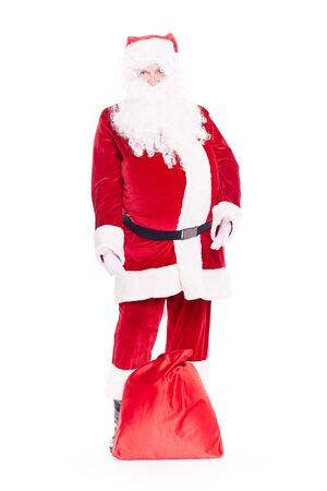 Portrait of Christmas character Santa Claus in traditional costume with red sack on white background Stock Photo