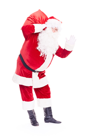 Portrait of Christmas character Santa Claus in traditional costume with red sack on white background Reklamní fotografie