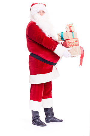 Isolated portrait of Santa Claus holding heap of Christmas gift boxes Stockfoto