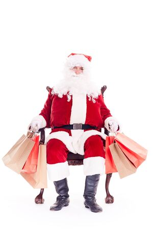 Santa sitting in chair and holding bunches of bags after Christmas shopping Stock Photo