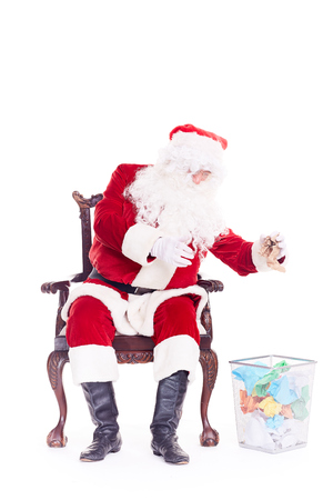 Bad Santa Claus reading letters from kids, crumpling them and throwing into trash basket