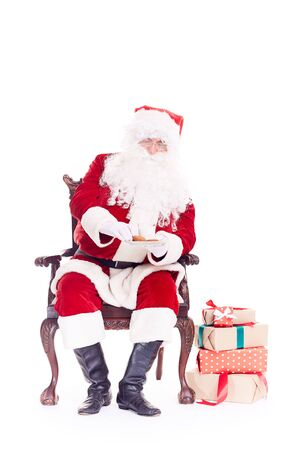 Portrait of Santa Claus sitting in chair and eating cookies isolated on white