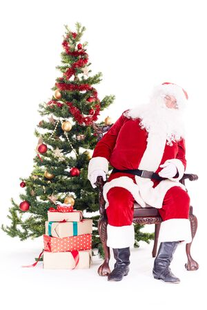 Portrait of Santa Claus sleeping in chair next to Christmas tree, heap of gift boxes near him