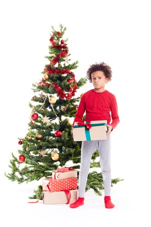 Portrait of cute mixed race little boy standing near Christmas tree with gift box in his hands