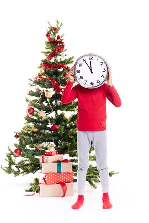 Portrait little boy standing near Christmas tree holding clock showing five minutes to twelve