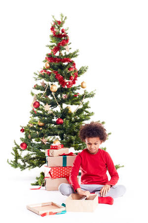 Portrait of cute mixed race little boy unpacking gifts near Christmas tree and taking digital tablet out of box