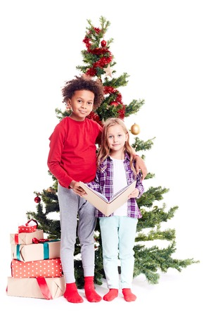 portrait of diverse brother and sister standing near christmas tree and reading book together stock photo