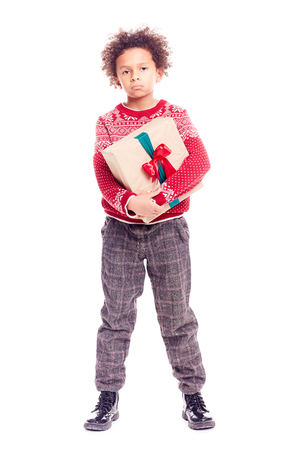 Portrait of curly-haired mixed-race little boy holding Christmas gift box