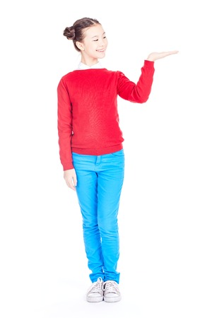 Portrait of cute Asian school girl in red sweater and blue jeans with double buns on her head holding something on her hand on white background