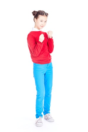 Portrait of cute Asian school girl in red sweater and blue jeans with double buns on her head posing on white background Stock Photo