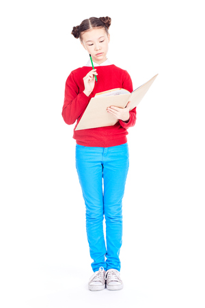 Portrait of Asian girl holding open textbook and pencil on white background