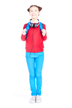 Portrait of Asian school girl posing on white background with backpack and headphones around her neck