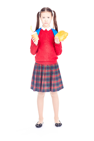 Portrait of Asian schoolgirl in uniform holding lunchbox and paper cup with drinking straw