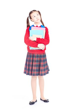 Portrait of female elementary student in school uniform holding notebooks and textbooks