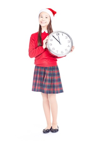 Isolated portrait of girl wearing school uniform and Santa hat holding clock showing five minutes to twelve