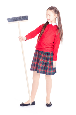 Portrait of girl in school uniform holding broom on white background