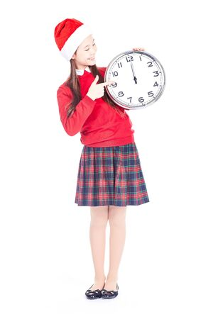 Isolated portrait of girl wearing school uniform and Santa hat holding clock showing twelve