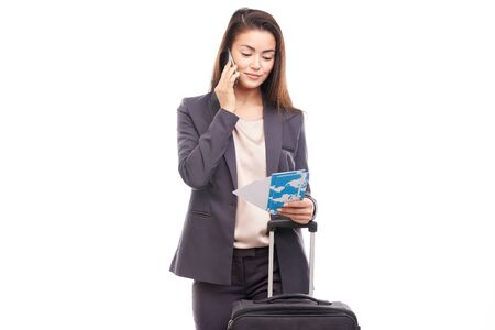 Portrait of young businesswoman posing with her suitcase before departure