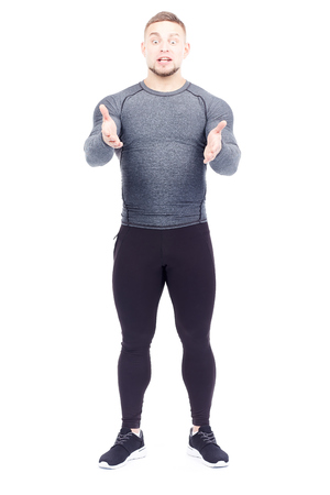 Portrait of handsome well-muscled gym instructor in sports tights and rashguard posing on white background