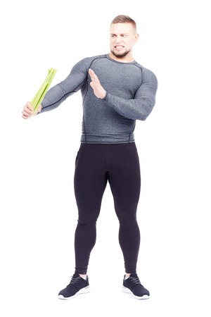 Portrait of handsome sporty man holding fresh celery isolated on white