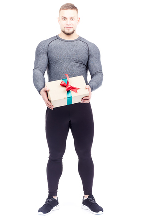 Portrait of well-muscled athlete posing with gift box on white background