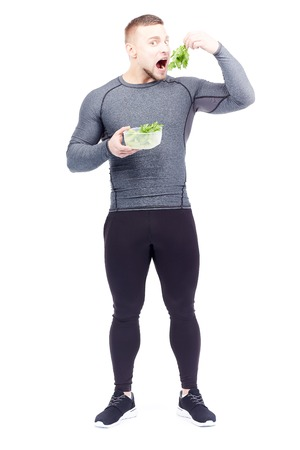 Full-length portrait of well-muscled male athlete holding lunch box with fresh celery