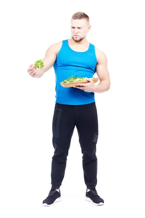 Fit man in sports clothes holding plate with fresh celery, portrait isolated on white Фото со стока