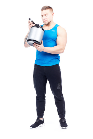 Isolated portrait of well-muscled athletic man holding container with sports nutrition Stock Photo