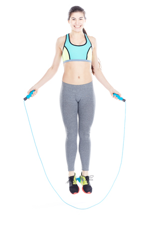 Portrait of attractive female gym goer exercising with skipping rope on white background
