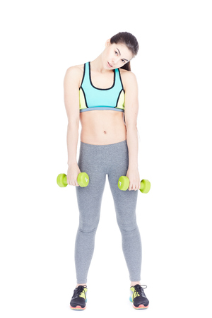 Portrait of attractive female gym goer exercising with dumbbells on white background 스톡 콘텐츠