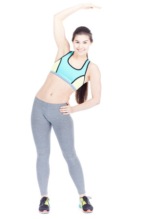 Portrait of attractive female gym goer exercising on white background