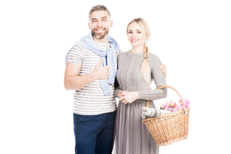 Young casual couple standing on white background. Young man showing thumbs up