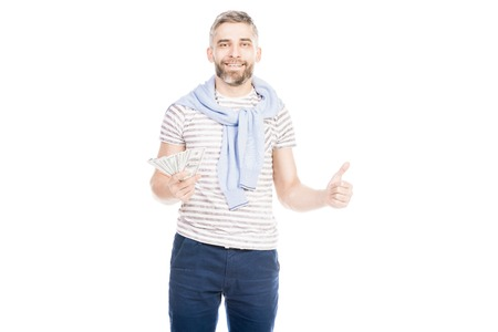 Portrait of smiling young man holding US paper currency isolated over white background