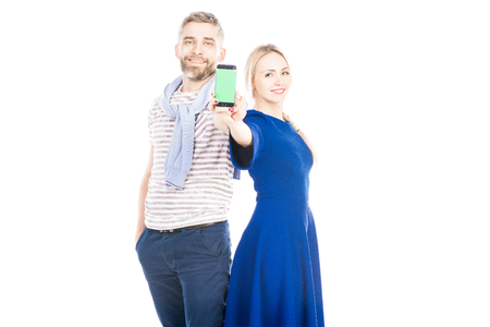 Portrait of young couple Holding smartphone on white background Фото со стока