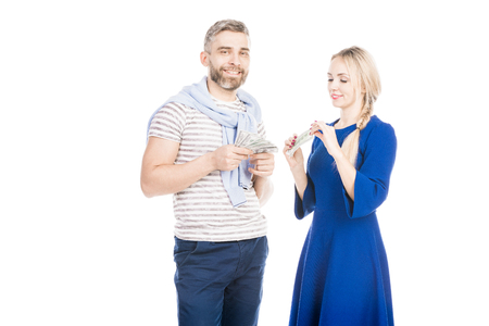 Young couple standing with US currencies on white background