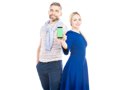 Casual couple showing phone on white background