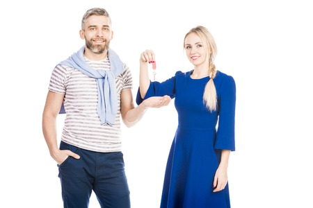 Portrait of young happy couple holding keys on white background Фото со стока