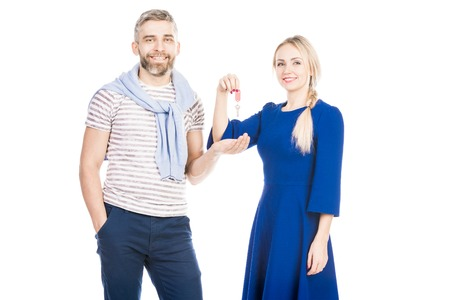 Young man receiving keys from woman on white background Фото со стока