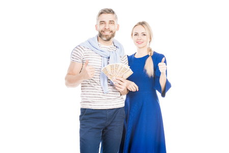 Happy couple with money standing on white background