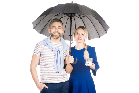 Portrait of friendly couple with cardboard house standing under umbrella