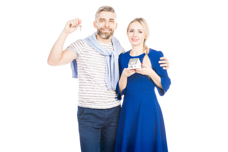 Happy couple holding house model and keys, standing isolated over white background
