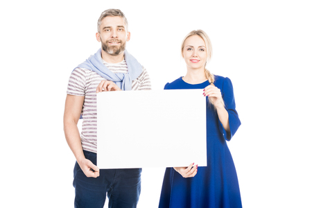Portrait of couple standing holding white billboard together, isolated on a white background.