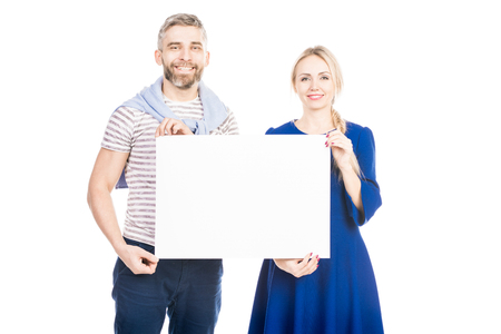 Portrait of a young beautiful couple holding a white cardboard, isolated on white background