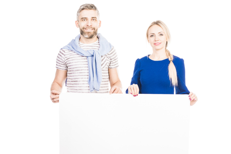 Portrait of couple holding blank sheet on white background Фото со стока