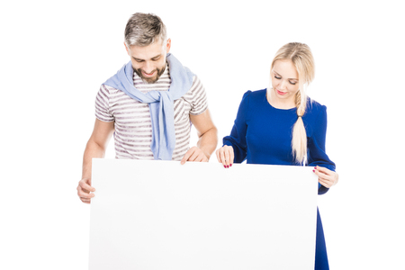 Young couple holding and looking down at blank white sheet